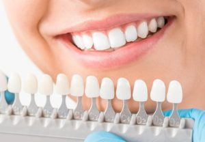 woman smiling behind dental crowns