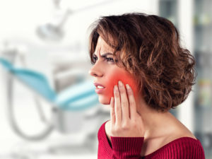 Woman with painful dental implant failure in dental office